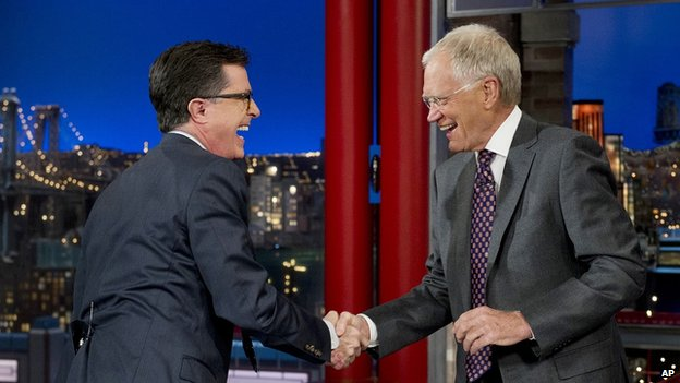 Stephen Colbert shakes late night host David Letterman's hand.