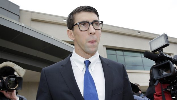 Olympic swimmer Michael Phelps walks out of a courthouse after pleading guilty to drunken driving, Friday, Dec. 19, 2014, in Baltimore