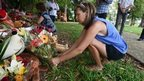 A woman lays flowers in memory of eight children murdered in Cairns