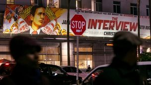 "People walk past a banner for ""The Interview"" in Los Angeles, California, on 17 December 2014"