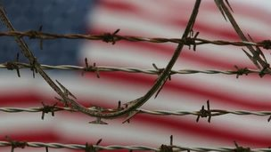 A US flag behind barbed wire at Guantanamo Bay. File photo