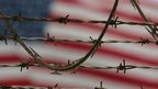 A US flag behind barbed wire at Guantanamo Bay. File photo
