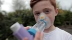 Boy using asthma inhaler