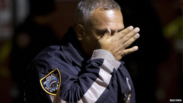 A policeman wipes a tear off his face after the shooting of two officers in New York
