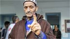 A Tunisian displays the indelible ink mark on his finger after he casts his ballot in a polling station during a presidential election in Tunis, Tunisia