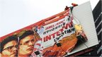 """Workers remove the poster for """"The Interview"""" from a billboard in Hollywood, California, December 18, 2014"""