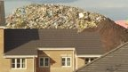 House with rubbish behind it