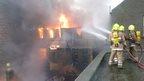 firefighters hosing flames