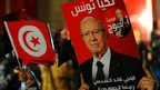 A supporter holds poster of Beji Caid Essebsi in Tunis, 21 December