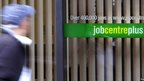 Blurred image of man walking past Job Centre