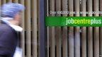 Blurred image of man walking past Job Centre