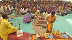 An Indian tribesperson (R, foreground) participates in a conversion ritual of some 200 Christians into Hinduism, at Aranai Village in Valsad district of Gujarat state, some 350 kms from Ahmedabad, on December 20, 2014.