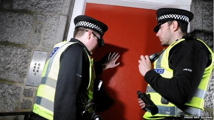 Two police officers at a door