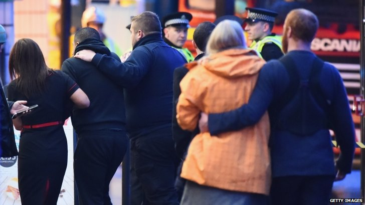 Members of the public comfort each other after the incident in George Square