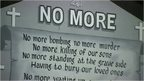 A mural in NI reading: 'No more. No more bombing no more murder, No more killing of our sons, No more killing of our sons, No more standing at the graveside, Having to bury our loved ones'