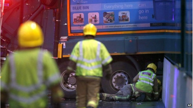 Firefighters on the ground next to a crashed bin lorry