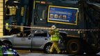 A firefighters walks close to a crashed bin lorry and a damaged car