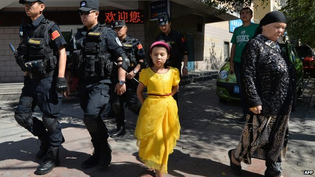 Armed Chinese police patrol the streets of the Muslim Uighur quarter in Urumqi on 29 June, 2013