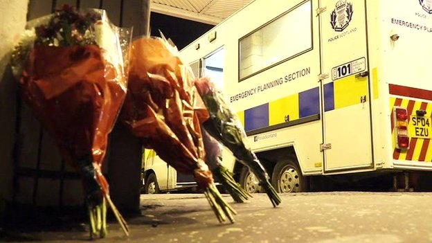 Flowers left on the ground, with a police vehicle visible in the background