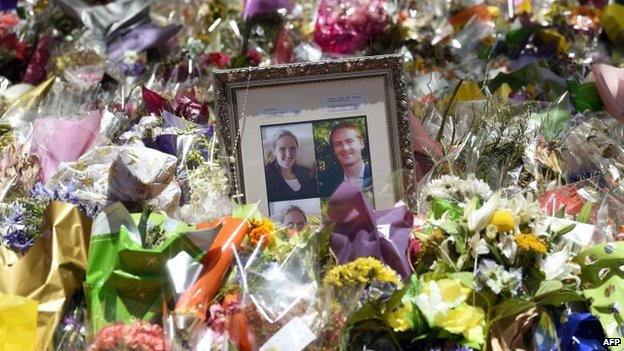 Photos of Katrina Dawson (left) and Tori Johnson (right) amongst floral tributes left outside the Lindt Cafe in Sydney's Martin Place (22 December 2014)