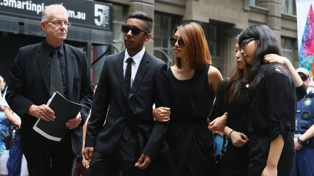 Fellow hostages Joel Herat (2nd L), Elly Chen (2nd R) and Fiona Ma (R) pay their respects at wreath laying ceremony after the funeral for Tori Johnson at Martin Place, Sydney (23 December 2014)