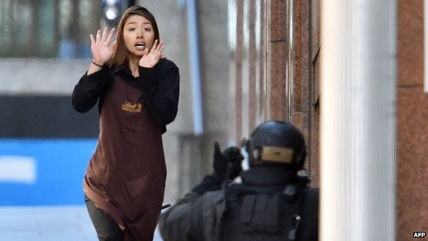 A hostage runs towards an armed police officer after escaping the cafe siege in Sydney (15 December 2014)
