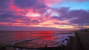 A bright pink and purple sky over sea lapping at the shore.
