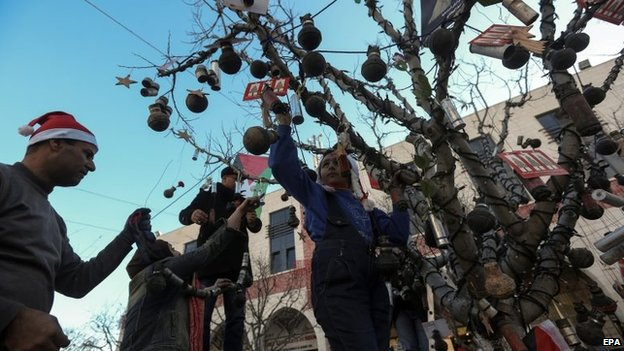 Palestinian activists decorate a Christmas tree with empty tear-gas canisters in Manger Square, Bethlehem