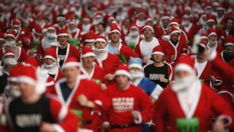Crowd in santa suits running