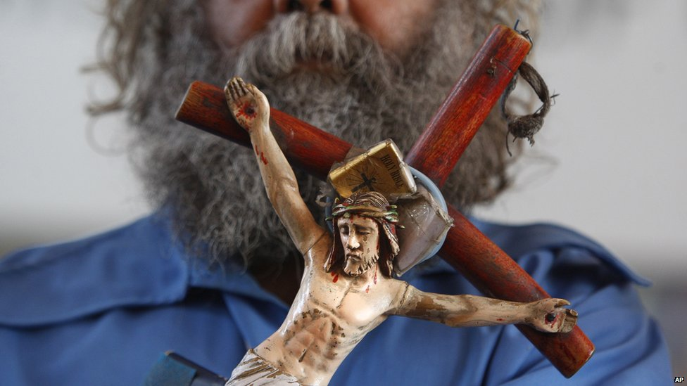 An Indian Christian holds a crucifix during Christmas prayers at St Mary's Garrison church, in Jammu, India, Thursday, Dec. 25, 2014
