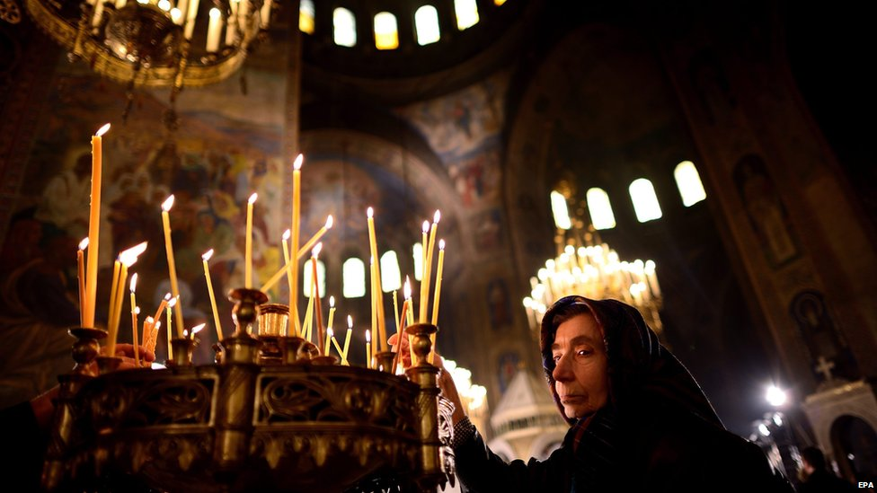 An elderly woman lights a candle during the Christmas Holy mass at the St Alexander Nevski Cathedral in Sofia, Bulgaria on Christmas Day, 25 December 2014