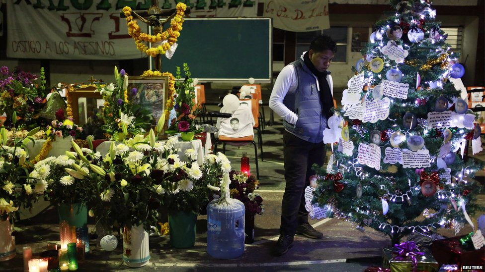 A man looks at a Christmas tree, with pictures of the 43 missing trainee teachers, next to an altar in the Ayotzinapa Teacher Training Raul Isidro Burgos College in Ayotzinapa, on the outskirts of Chilpancingo, Guerrero, December 24, 2014. Mexican authorities on December 7 said that mounting evidence and initial DNA tests confirmed that 43 trainee teachers who were abducted in Iguala by corrupt police on September 26 were incinerated at a garbage dump by drug gang members.