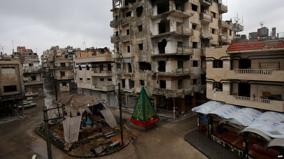 A crib made out of rubble and a Christmas tree are set on a roundabout in the regime-held Hamedieh neighbourhood in the Syrian city of Homs on December 22, 2014, as Christians around the world prepare to celebrate the holy day.