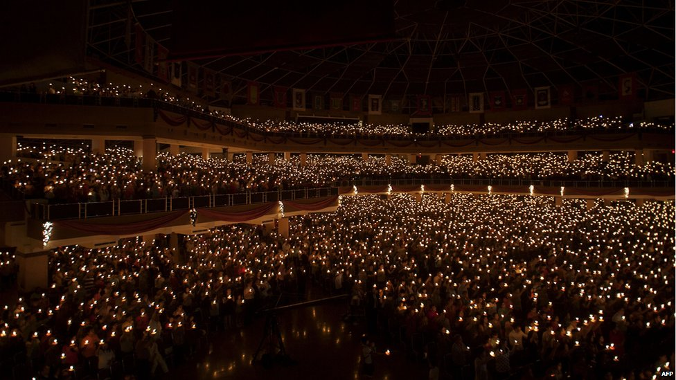 In this picture taken on December 24, 2014 Christians hold candles during the mass service in Surabaya, in the eastern Java island. Millions of Christians in Indonesia celebrated Christmas eve in the most populous Muslim country.