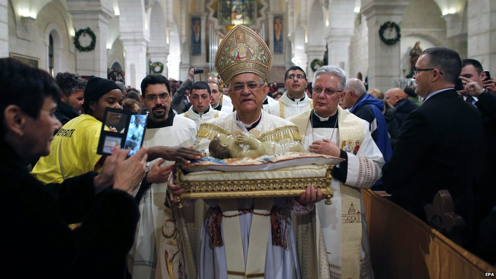 The Latin Patriarch of Jerusalem Fouad Twal carries a statuette of baby Jesus during a Christmas Midnight Mass at the Church of the Nativity in Bethlehem, the West Bank, 25 December 2014