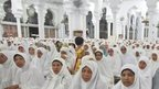 Acehnese women attend a prayer for the victims of Indian Ocean tsunami ahead of its 10th anniversary at Baiturrahman Grand Mosque in Banda Aceh, Aceh province, Indonesia
