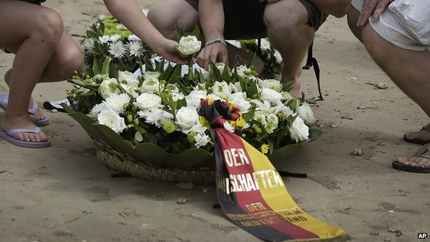 Relatives and friends of German victims of the Asian tsunami lay white roses on the beach during a commemoration and religious ceremony for German, Austrian and Swiss victims in Khao Lak, Thailand, Friday, Dec. 26, 2014