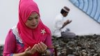 A woman prays at a mass grave in Aceh, Indonesia, 26 Dec