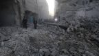 "People inspect a site hit by what activists said was a barrel bomb dropped by forces loyal to Syria""s President Bashar al-Assad on al-Marjeh neighborhood of Aleppo November 12, 2014"