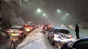 A queue of cars on a snowy road