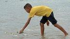 A boy lays a flower in water