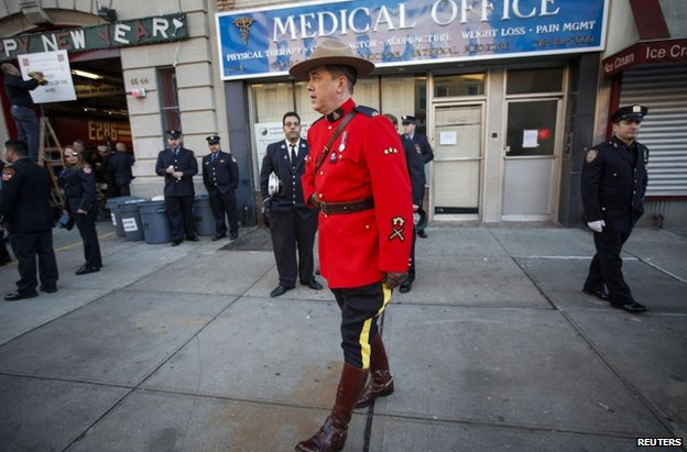 A member of the Royal Canadian Mounted Police stands with other policemen lining the streets near the Christ Tabernacle Church, 27 December