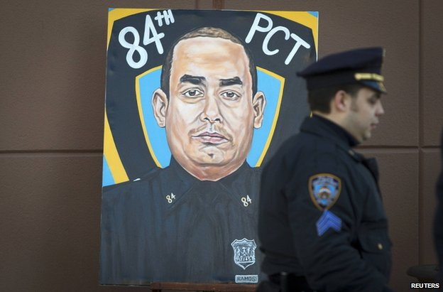 A police officer walks past a painting of NYPD officer Rafael Ramos in his funeral at Christ Tabernacle Church, 27 December