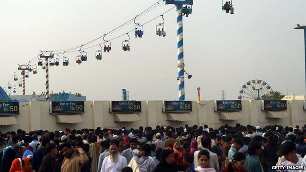 Pakistani Muslims gather at a fairground as they celebrate Eid al-Fitr in Karachi on 30 July 30, 2014