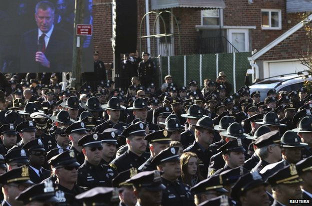 Officers turn their backs on Mayor Bill de Blasio outside the church in New York, 27 December