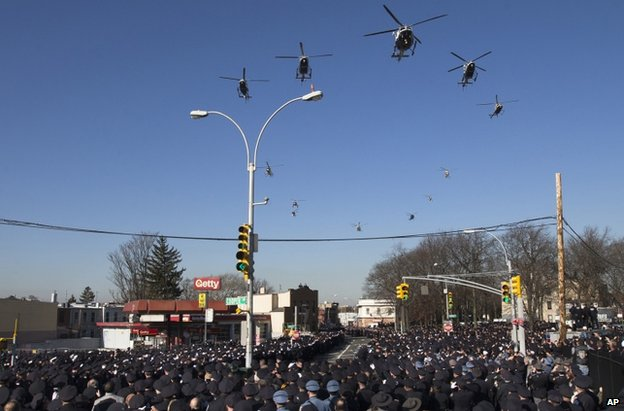 Police helicopters fly over the funeral procession in New York, 27 December