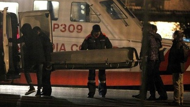 The Italian coast guard carries a body during an operation to rescue a stricken Italian ferry