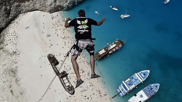 Lukas Michul  jumps from atop the rugged rocks overlooking the azure waters of Navagio beach, Greece