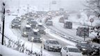 Snow fall as cars move bumper-to-bumper