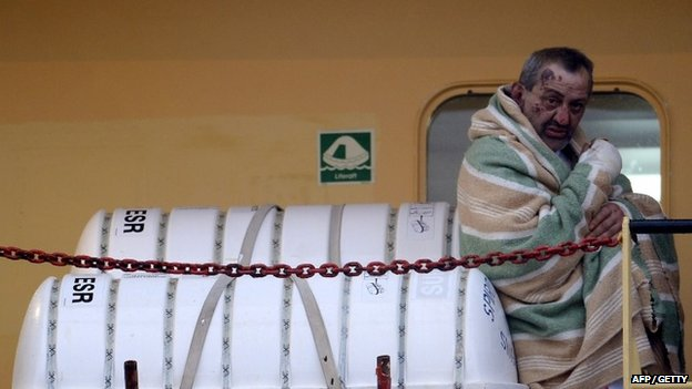 """A wounded passenger among 49 survivors evacuated from the burning ferry """"Norman Atlantic arrives aboard a cargo container ship to the harbour of Bari on December 29, 2014."""